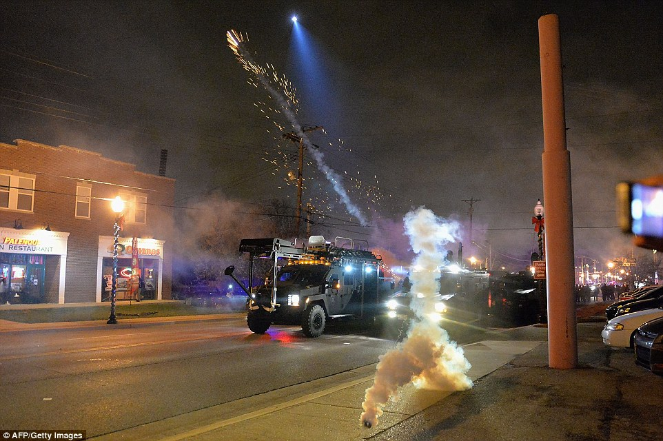Show of force: Police fire canisters of tear gas from armored vehicles as demonstratos move on to the streets in Ferguson