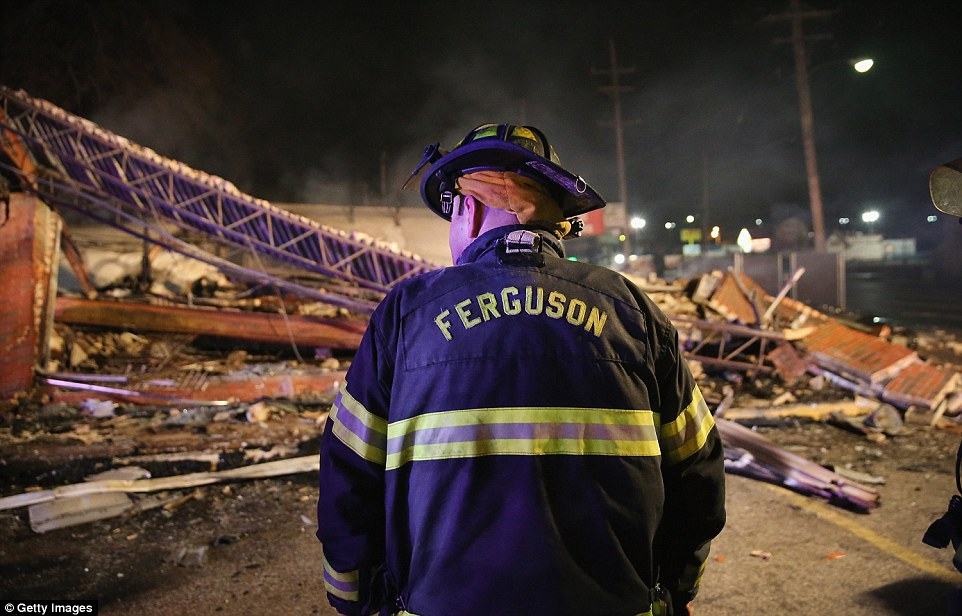 Wrecked: A Ferguson firefighter surveys rubble at a strip mall that was set on fire when rioting erupted
