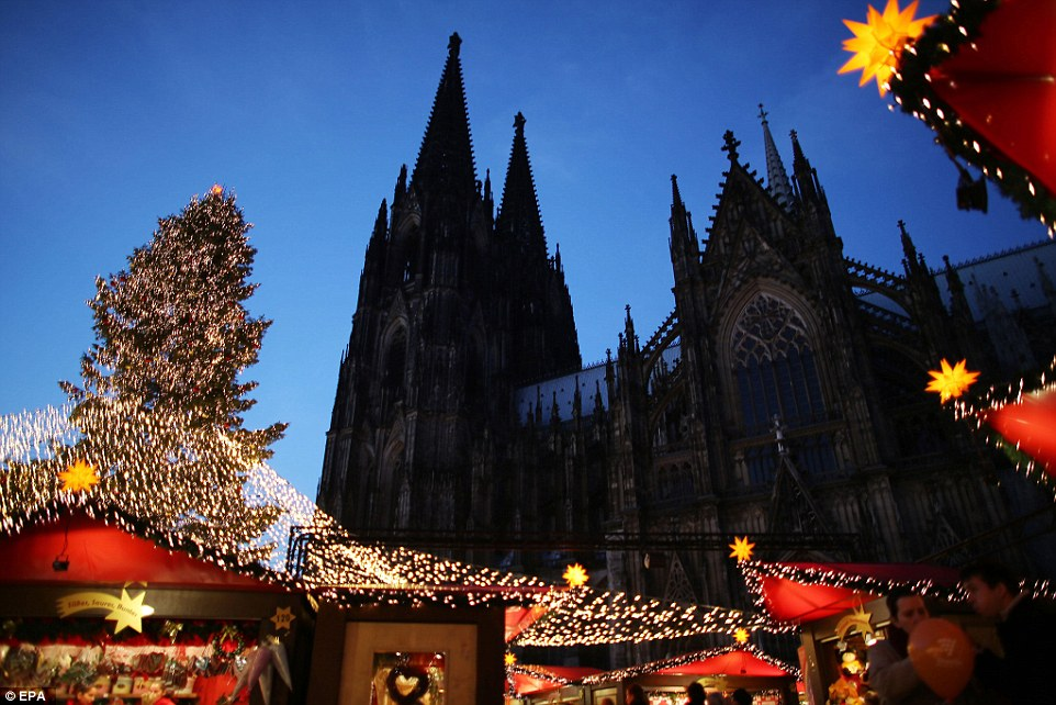 Stunning backdrop: People walk by the cathedral at the Christmas market in Cologne, Germany