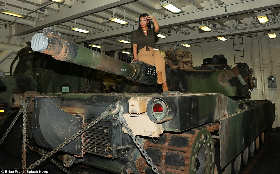 The perfect photo op: Kim climbed on top of a tank for a snap as she gave a salute to the cameras