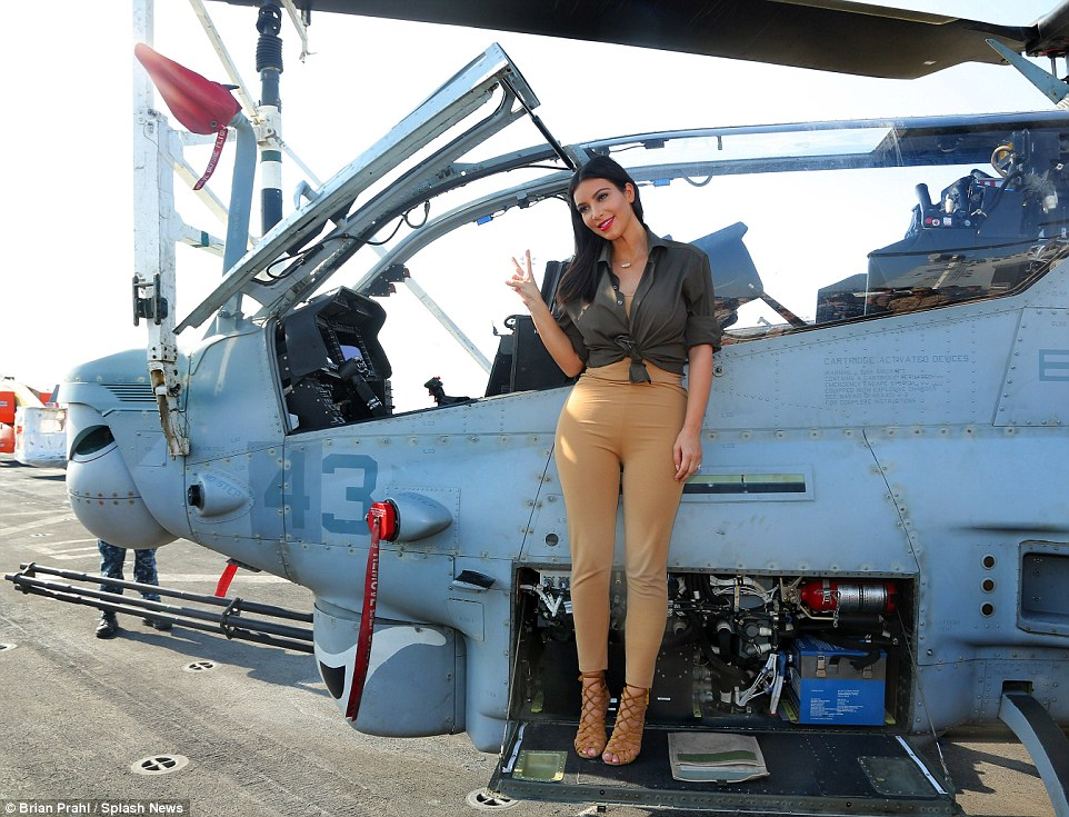 Weapon of mass distraction! Kim Kardashian showed off her curves in camo as she posed beside an airplane on board the USS San Diego in Dubai