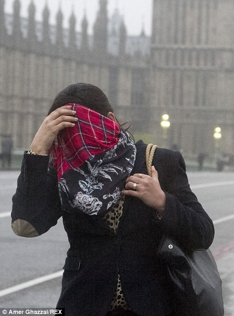 A pedestrian covers her face from the rain in London today