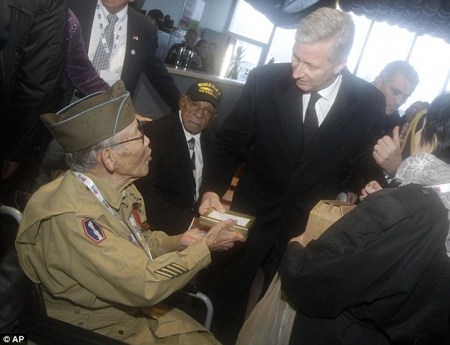WWII veteran Bob Izumy of the 101st AB 506, left, hands over a gift to King Philippe during the celebrations