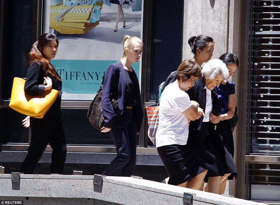 Women help an elderly lady as they are evacuated by NSW Police from Martin Place