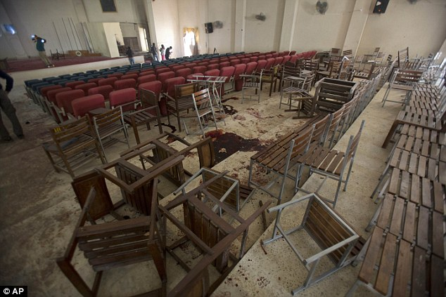 Chairs are upturned and blood stains the floor at the Army Public School auditorium