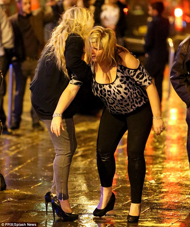 Hospitals were on high alert as Britons put their health and safety at risk by opting for one drink too many, pictured a woman falling over in Manchester