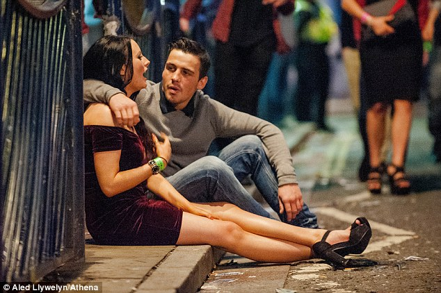 A couple chat on the pavement during the busiest night of the Christmas party season and the year's booziest evening