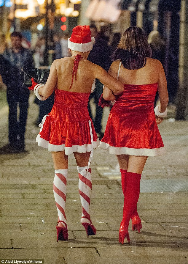 Two women dressed in sexy Santa outfits walk down Swansea's Wind Street for a Black Friday night out