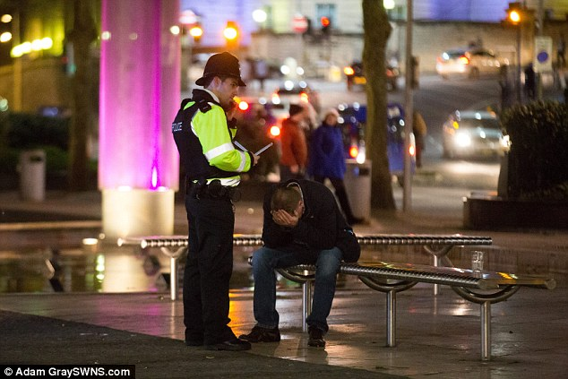 A man sits with his head in his hands as he is dealt with by a police officer in Bristol city centre