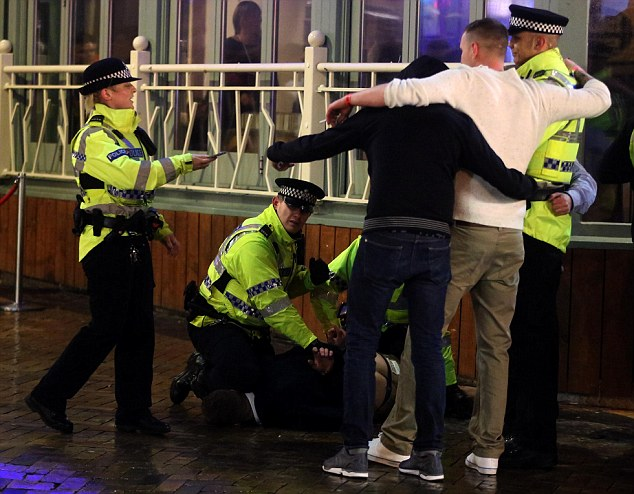 As her colleagues struggle with the man on the floor, the policewoman hands a phone back to two revellers posing with another police officer