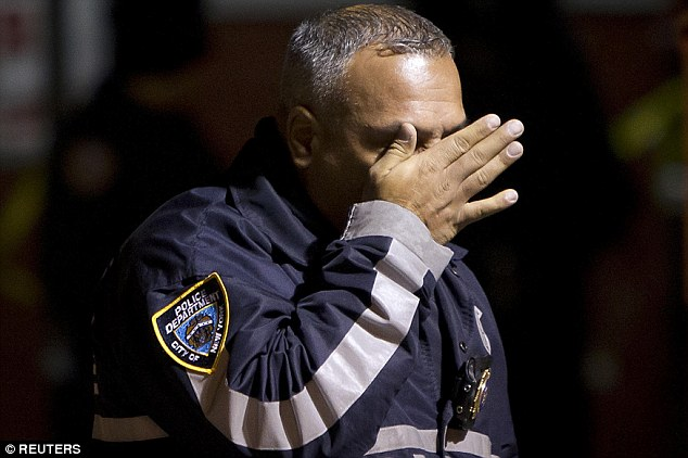 Emotional: A police officer wipes tears away from his face as he walks away from the scene of a shooting