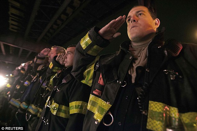 Stand and salute: New York Fire Department personnel salute as an ambulance and motorcade carrying one of the two New York Police officers who were shot dead passes by a New York Fire Department honor guard