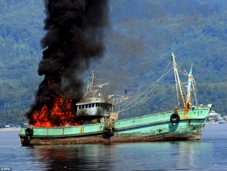 One of the ships burns. The two vessels carried 63 tonnes of fish and shrimp. 62 crewmen, mostly Thai, were arrested and several were turned over to immigration. They were caught on December 7 near the sea border of Indonesia and Papua New Guinea