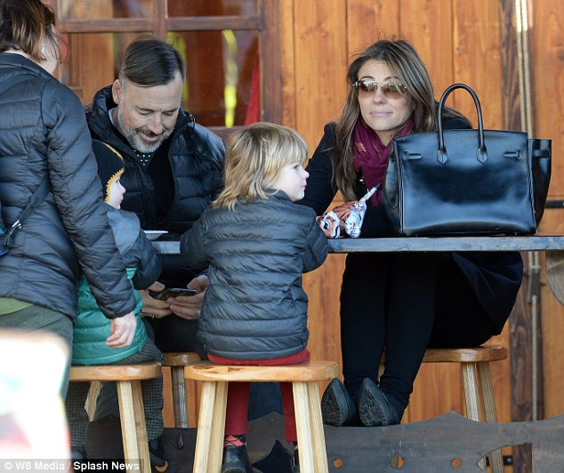 Feet up: Moviestar Liz sat with her feet perched under the table as she sat on a stool at the bench