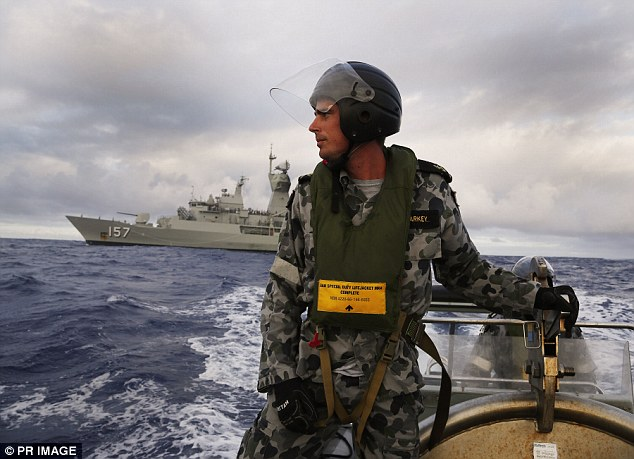 Leading Seaman, Boatswain's Mate, William Sharkey searches for debris on a rigid hull inflatable boat in the Southern Indian Ocean in April. In the background is HMAS Perth, which was involved in the search