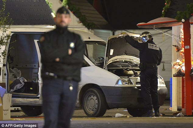 A bomb disposal unit observes the engine of the van left at the scene in Nantes where dozens were injured