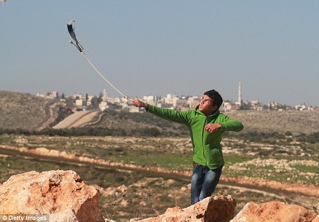 A Palestinian throws stones against Israeli security forces during the protest against the separation barrier