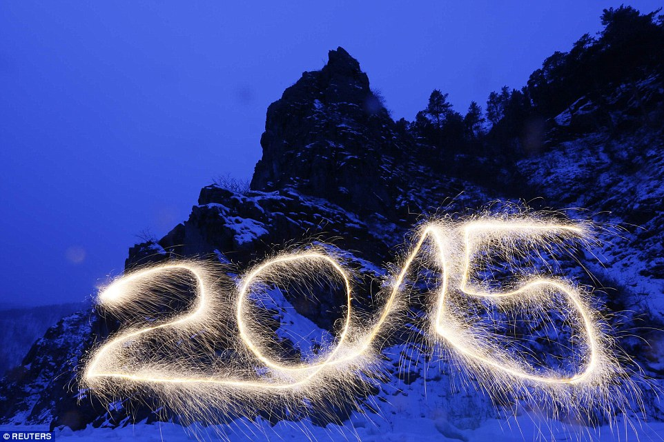 Incoming: 2015 is written in the air with a sparkler at the frozen Mana River in the Taiga district outside Russia's Siberian city of Krasnoyarsk