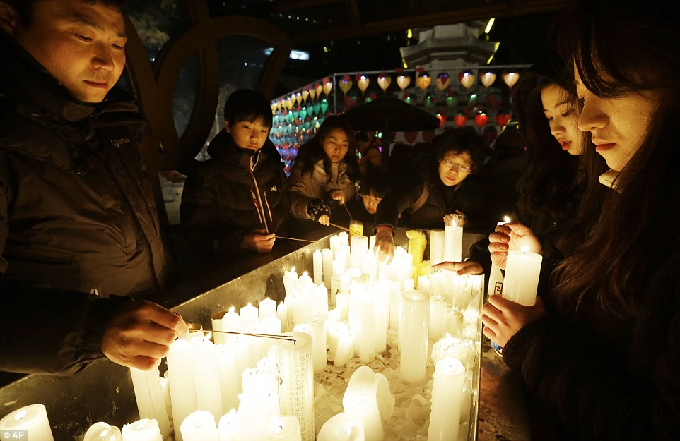 Moment of peace: Buddhists light candles during New Year celebrations at Jogye Buddhist temple in Seoul, South Korea