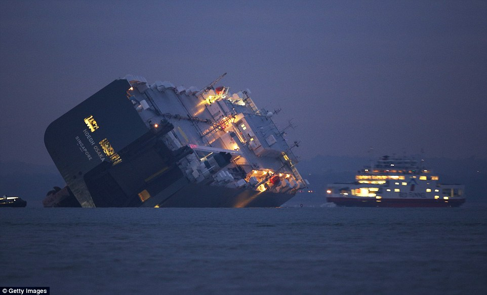 A car ferry passes the stricken Hoegh Osaka cargo ship after it ran aground on a sand bank. All 25 crew members were rescued overnight