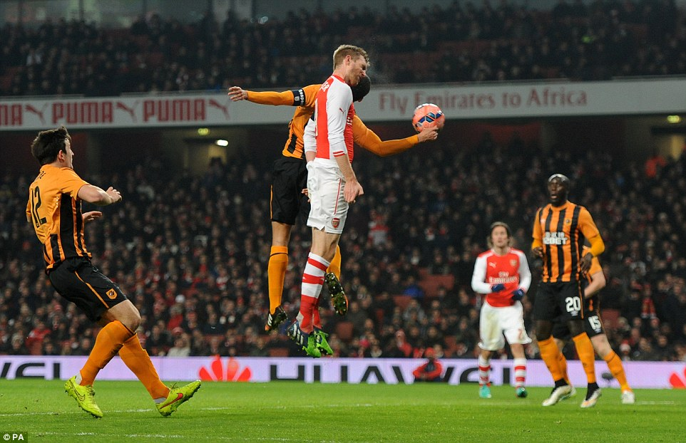 Arsenal defender Mertesacker rises beats Hull captain Curtis Davies to win a header from a corner