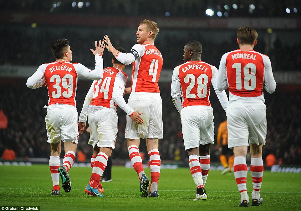 Arsenal players rush to congratulate Mertesacker after the German centre-half opens the scoring