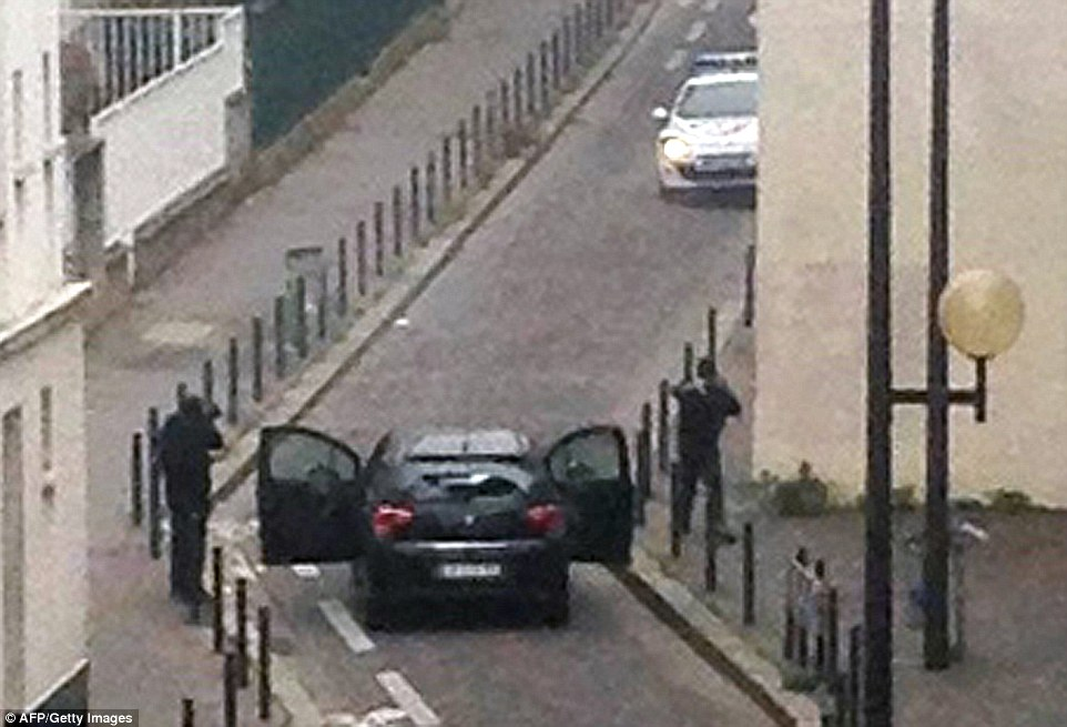 At large: The gunmen are seen near the offices of the French newspaper Charlie Hebdo before fleeing in a car. They remain on the loose