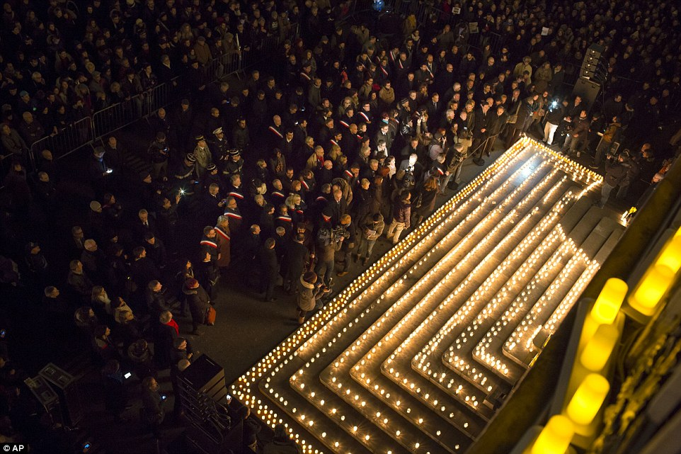 Touching: The steps of a public building in Lyon are lit with candles as thousands of people gather to show support for Charlie Hebdo