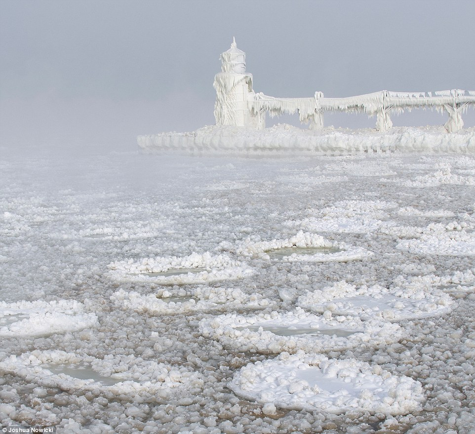 Stunning: This photo, captured by Joshua Nowicki, shows St Joseph Lighthouse and its pier, in Michigan, both of which are completely blanketed in white icicles. It also features a number of circular formations of ice - which Mr Nowicki dubs 'ice pancakes' - on the shore