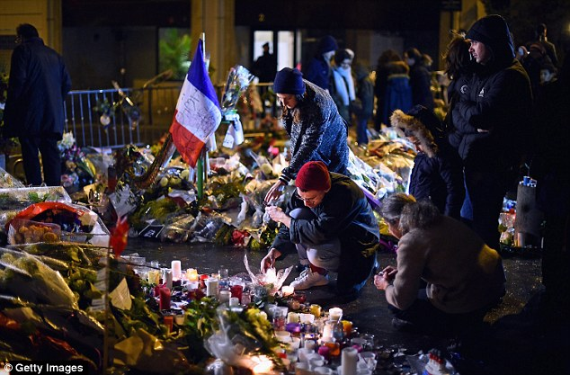 Members of the public light candles in tribute to the 17 dead in Paris following three days of terror attacks