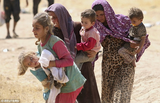 Human tragedy: Displaced people from the minority Yazidi sect, fleeing violence from forces loyal to the Islamic State in Sinjar town, walked towards the Syrian border last August 11, 2014
