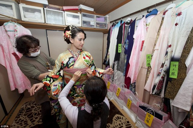 Anne Nakajima gets fitted into a kimono at 5:30 am at a beauty parlor in Isumi city, Chiba province. Many young women throughout Japan make appointments one year in advance to get their hair prepared and to be fitted into a kimono