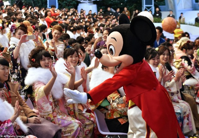 Disney character Mickey Mouse greets 20-year-old women wearing kimonos during their celebration at Tokyo Disneyland in Urayasu