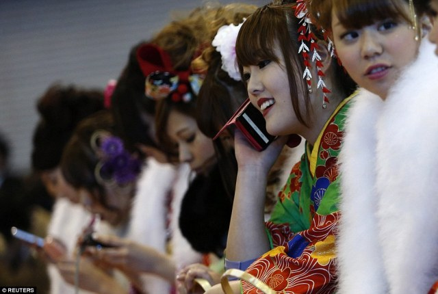 A Japanese woman in a kimono uses her mobile phone during a Coming of Age Day celebration ceremony at an amusement park in Tokyo