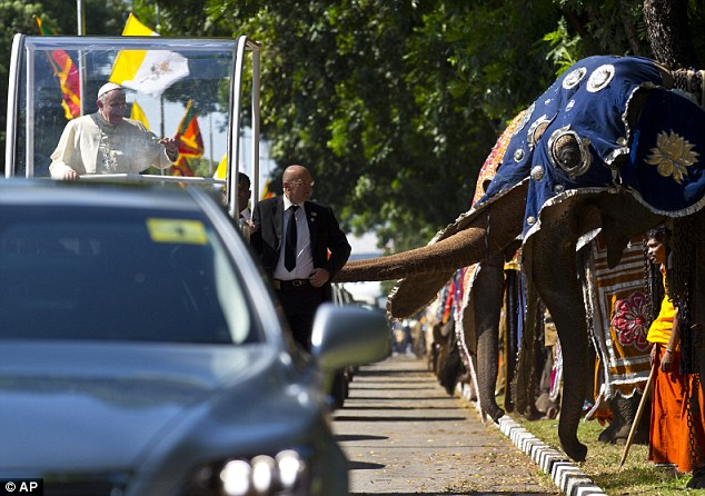 About 40 costumed elephants lined the airport road while a 21-canon salute boomed out before Francis spoke of 'finding true peace'