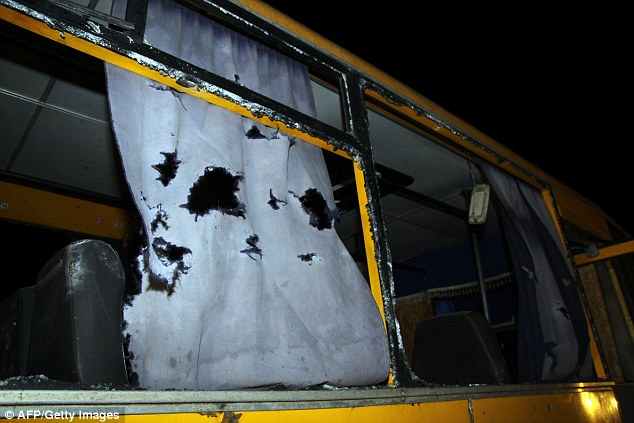 Curtains are left torn and damaged after the shell hit the bus near Donetsk, killing at least 11 civilians