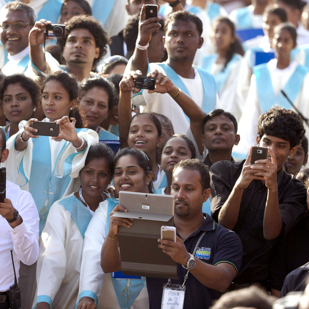 The faithfuls takes photos of Pope Francis as he arrives in Colombo's seafront Galle Face Green for the canonization ceremony of Joseph Vaz, Wednesday, Jan. ...