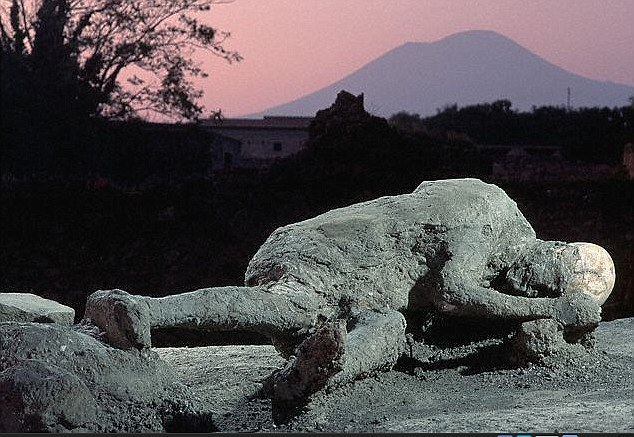The scroll is among hundreds retrieved from the remains of a villa at Herculaneum, which along with Pompeii (preserved victim pictured) was one of several Roman towns that were destroyed when Mount Vesuvius (pictured in background) erupted in 79AD