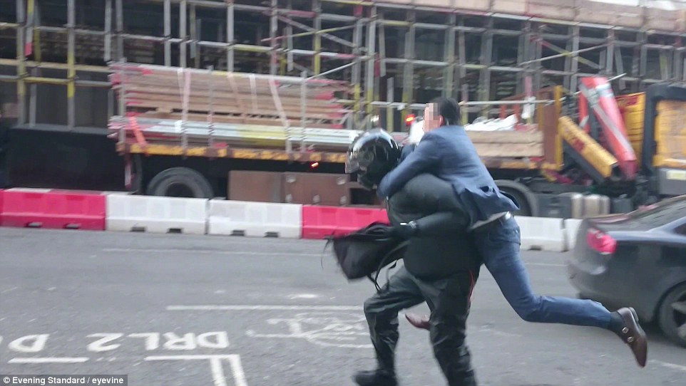 The have-a-go hero gets on the man's back, but is then threatened by the robber, who then runs off