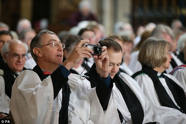 Capturing the moment: A priest takes a photograph as he waits for the start of the ceremony