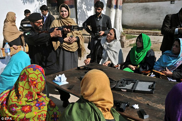 As the group of eight teachers listens intently, a weapons instructor demonstrates how to fire a Kalashnikov