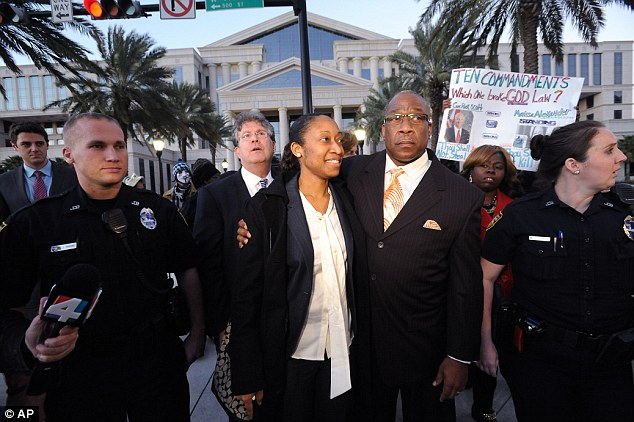 Free at last: Marissa Alexander walks by her dad Raoul Jenkins and is surrounded by her legal team and supporters after her sentencing in Jacksonville, Florida on Tuesday