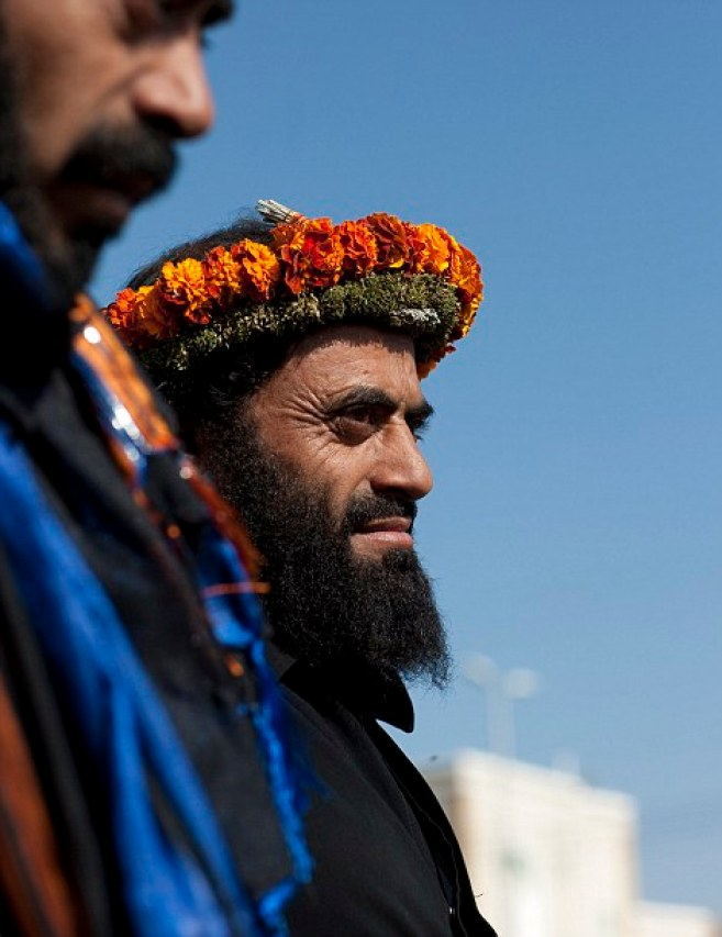 Elaborate: The men wear ornate garlands made from herbs and flowers growing wild in the foothills of the mountains