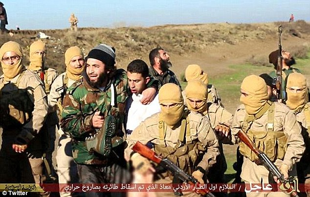Captured: Muath al-Kaseasbeh (centre in white) was captured by the Islamic State after after crashing near its HQ in the Syrian city of Raqqa in December. ISIS is now believed to brutally murdered him