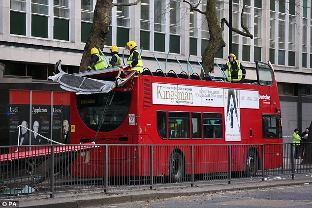 Workers from the London Fire Brigade investigate the ruined top deck of the bus