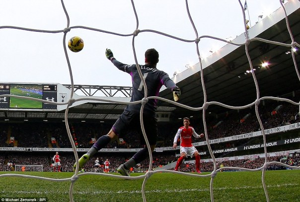 Tottenham goalkeeper Hugo Lloris dives in vein as Ozil unleashes a volley that flies into the top corner from about 12 yards out