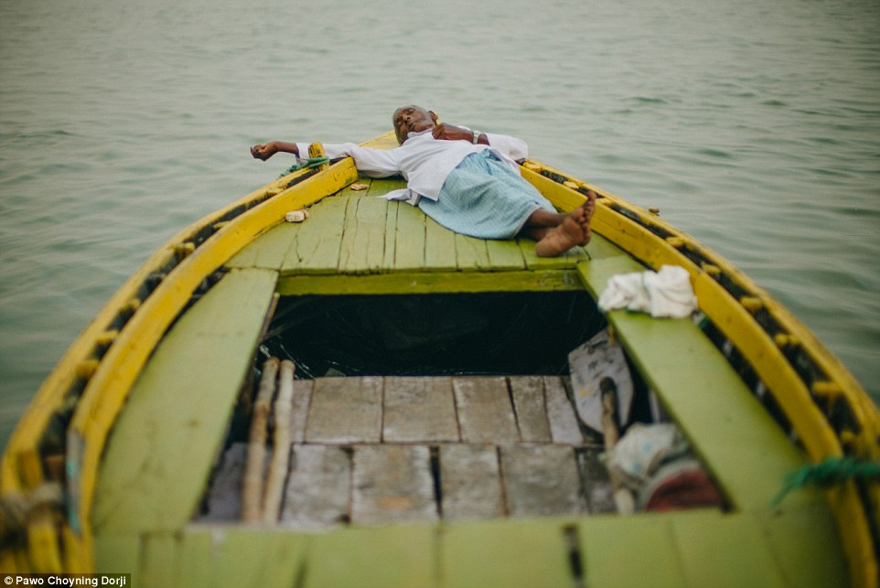 An elderly man snoozes on a traditional wooden boat. Until recently, Bhutan has been isolated due to geographical location, allowing it to retain its unique culture and heritage
