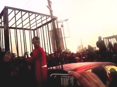 A terrified Kurdish prisoner looks out from his cage at a mob of jeering militants in the horrific scene