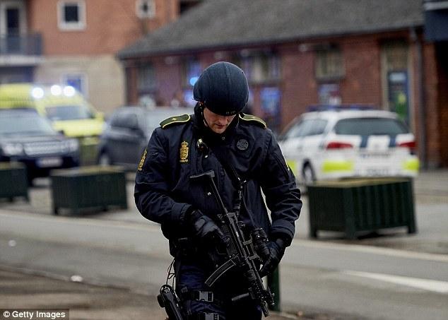 Protector de la situación: Un oficial de policía de Armas de Fuego está de guardia tras el tiroteo en Krudttonden café en Dinamarca