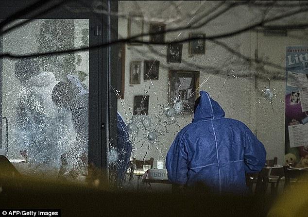 """Plagado: El tiroteo se produjo horas después de que un hombre murió cuando un """"fanático islamista 'abrió fuego contra un café dos millas de distancia.  Arriba, las ventanas de la cafetería Krudttoenden se hicieron añicos luego de ser despedidos con 200 balas"""
